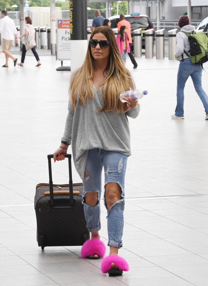 9fec0f348e167463b95fef3e0aaddc60 Katie Price can't be missed as she jets out of UK in bright pink fluffy slippers and very ripped jeans