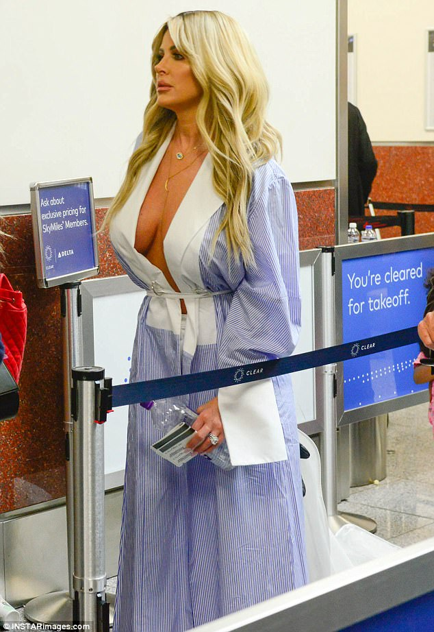 fcf13866ba69581c09140687b48ee70a Who needs an X-ray machine? Braless Kim Zolciak flaunts ample cleavage in a plunging belted jacket as she goes through security at Atlanta Airport