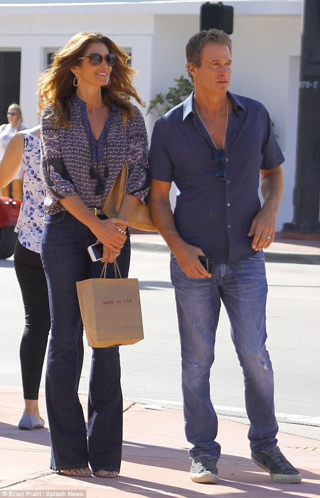 b357510f25761813f83fbb1cbc3a8ea7 Hippie chic! Cindy Crawford is every inch the boho babe in a paisley-print blouse and tight bell bottoms as she shops in Miami with Rande Gerber