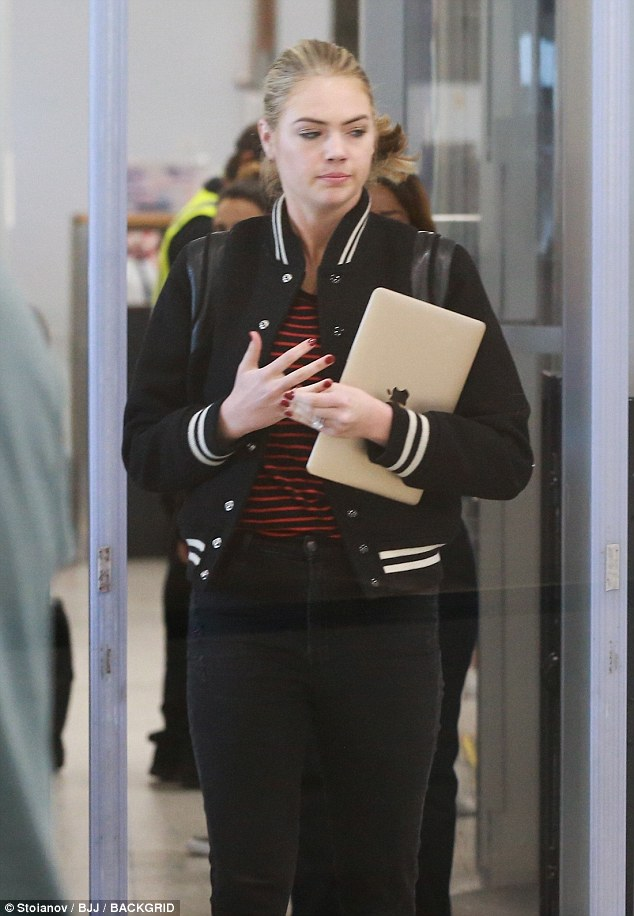 11df47182cd23243fd54347af8583f75 Kate Upton sports varsity jacket and skinny jeans at LAX while going through TSA check